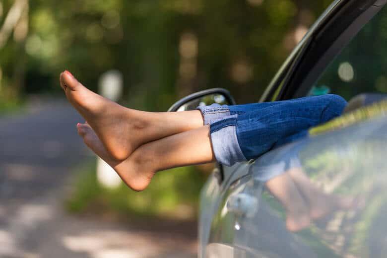 Füße hängen aus Auto