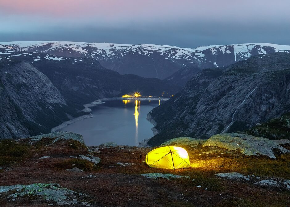 Yellow tent in norwegian mountains. Mountain lake at background. Sunset scene. Travel concept.