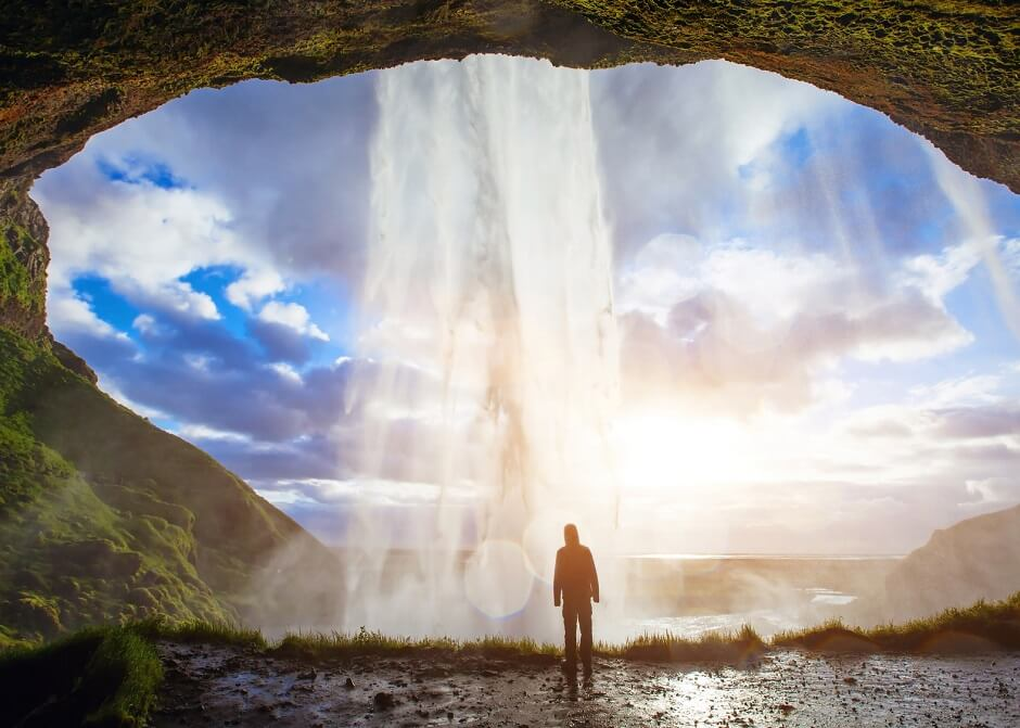 incredible waterfall in Iceland, silhouette of man enjoying amazing view of nature