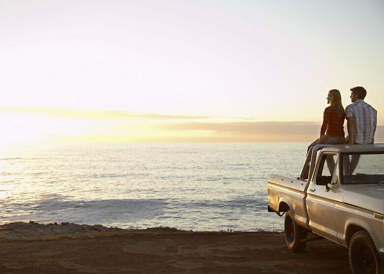Paar mit Auto am Strand