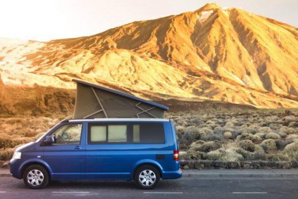 Blauer Minivan fährt Straße vor Bergkulisse entlang