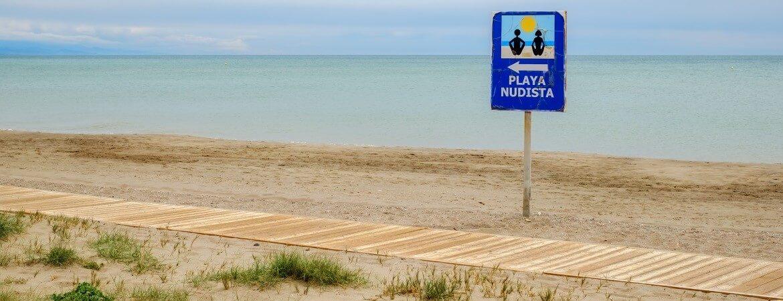 """Hinweisschild """"FKK-Strand"""" am Strand in Spanien"""