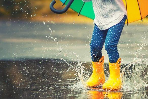 Kind mit gelben Gummistiefeln springt in Regenpfütze