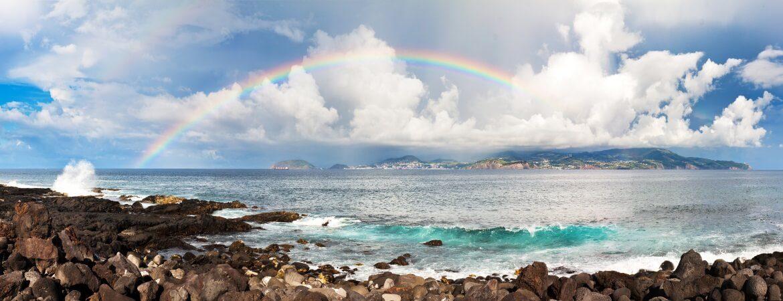 Regenbogen über Steinstrand auf den Azoren