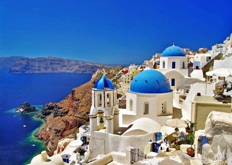 Küstenstadt Oia auf der griechischen Insel Santoria mit blauen Kuppeln, Meerblick