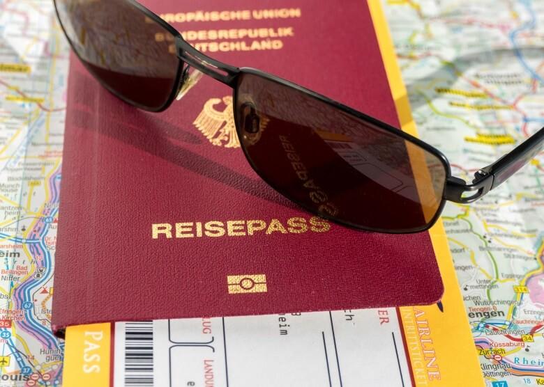 Reisepass, Flugticket und Sonnenbrille auf Weltkarte