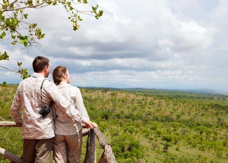 Pärchen in Safari-Kleidung blicken in die Ferne