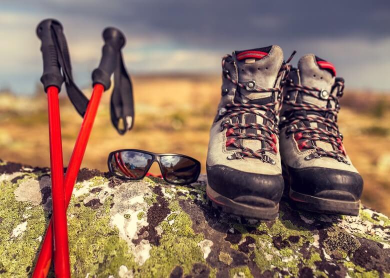 Safari-Kleidung: Wanderschuhe, Sonnenbrille und Wanderstöcke