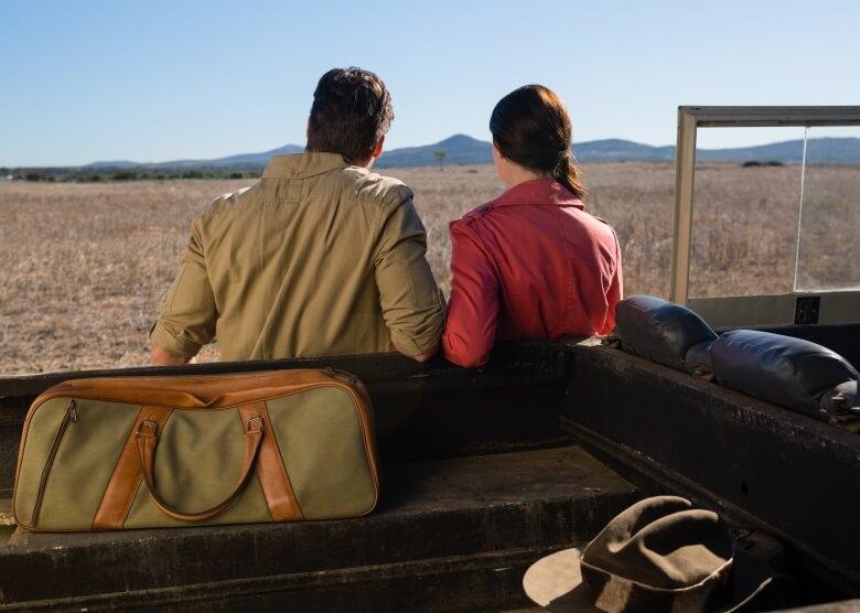 Pärchen mit Tasche und Auto auf Safari