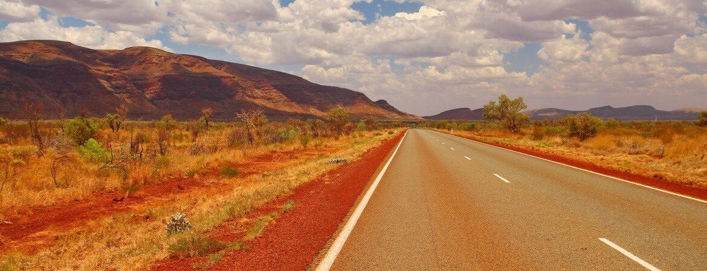 Straße an der australischen Westküste mit Bergen im Hintergrund