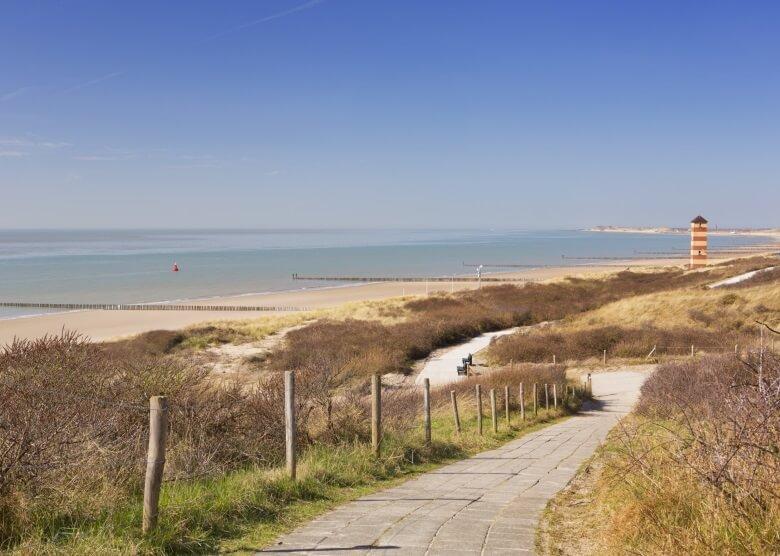 Strand in Zeeland in den Niederlanden mit Leuchtturm und Dünen