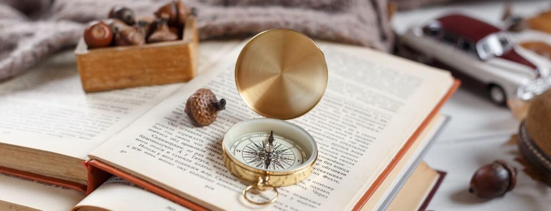 Aufeinandergestapelte Abenteuerbücher mit Kompass