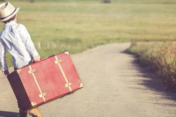 Junge reist alleine mit seinem Koffer