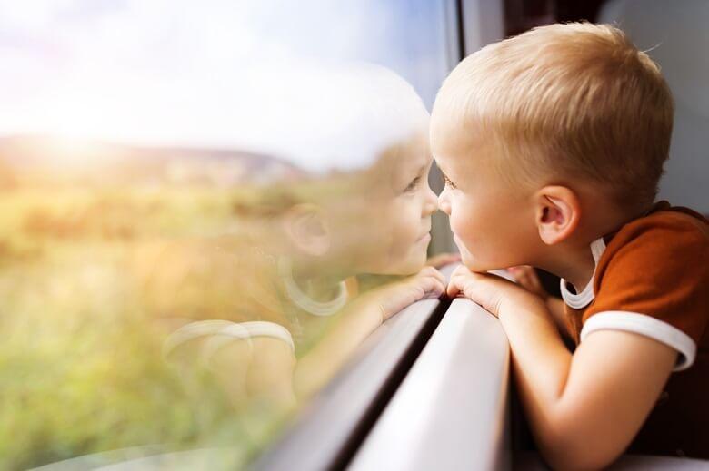 Kleiner Junge schaut aus dem Zugfenster auf die vorbeiziehende Landschaft