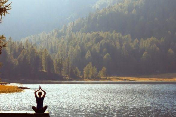 Frau macht Yoga an Waldsee