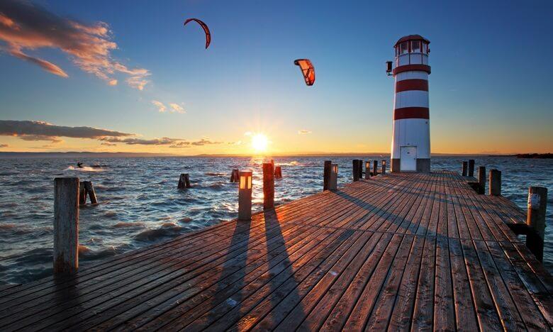 Steg mit Leuchtturm und Surfern am Neusiedler See in Österreich