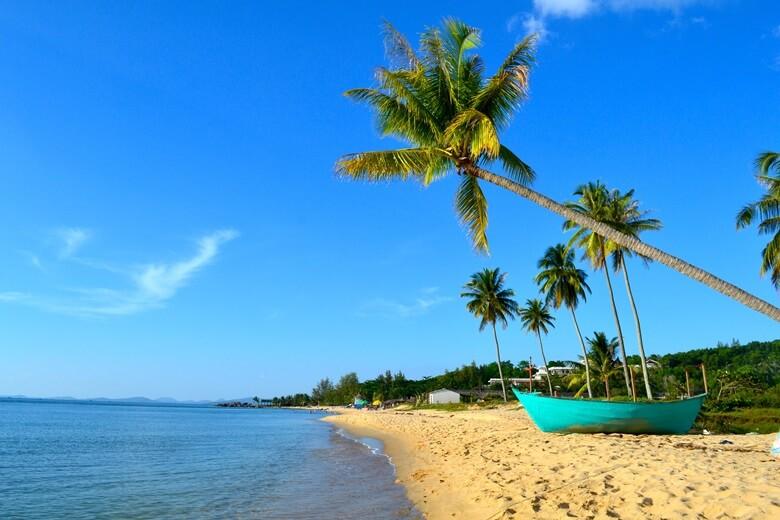 Strandabschnitt von Phu Quoc in Vietnam mit Palmen und Boot