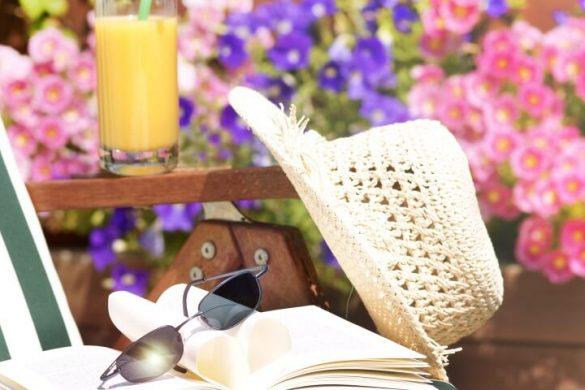 Gartenstuhl mit Buch, Sonnebrille und Hut