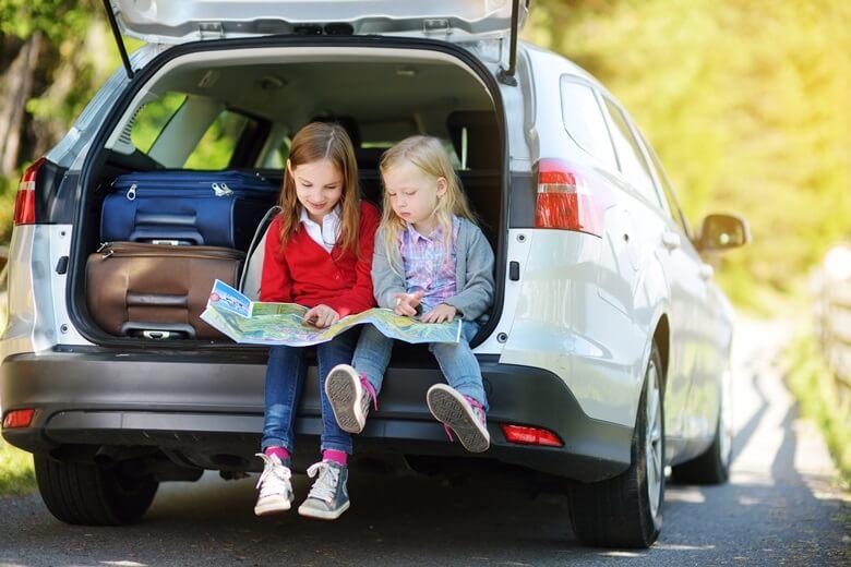 Zwei Mädchen sitzen im Kofferraum eines Familienwagens