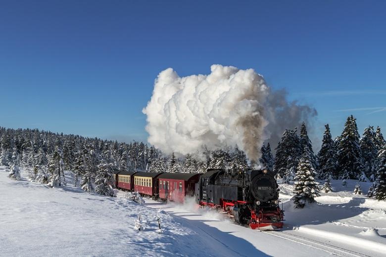Harzer Schmalspurbahn fährt durch die schneebedeckte Harzregion