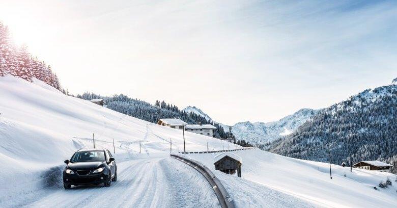 Auto fährt durch Schnee in den Bergen
