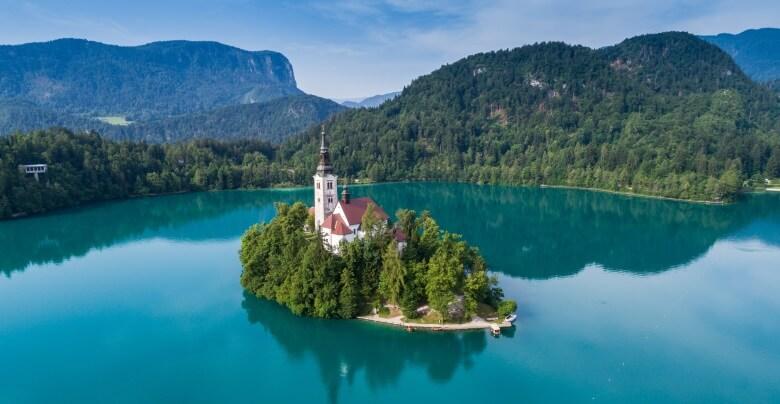 Blick über den klaren Bleder See mit Kirche Maria Himmelfahrt in Slowenien
