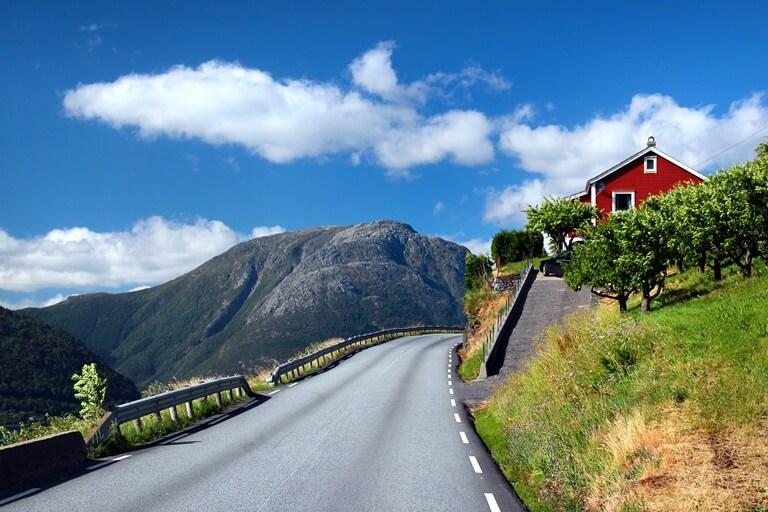 Straße mit Häuschen am Hardangerfjord in Norwegen
