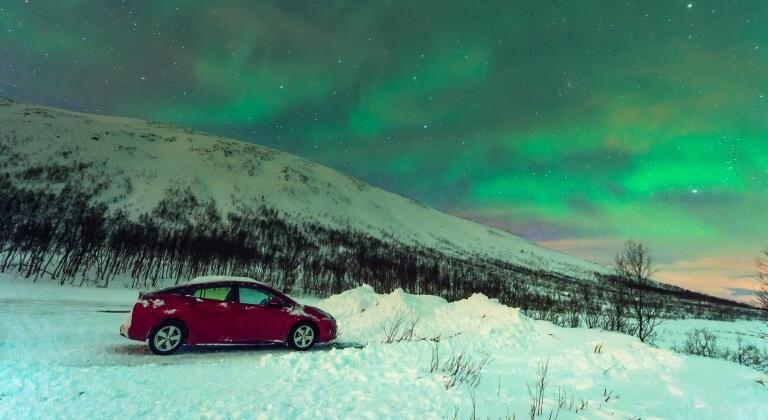 Auto unter den Polarlichtern in Norwegen