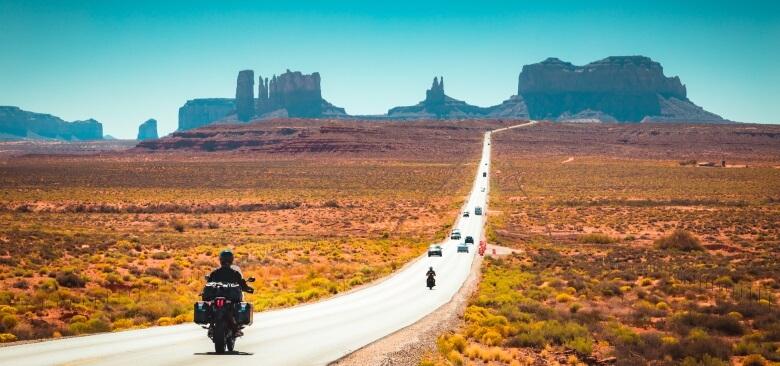 Motorradfahrer auf der Straße zu Monument Valley in den USA