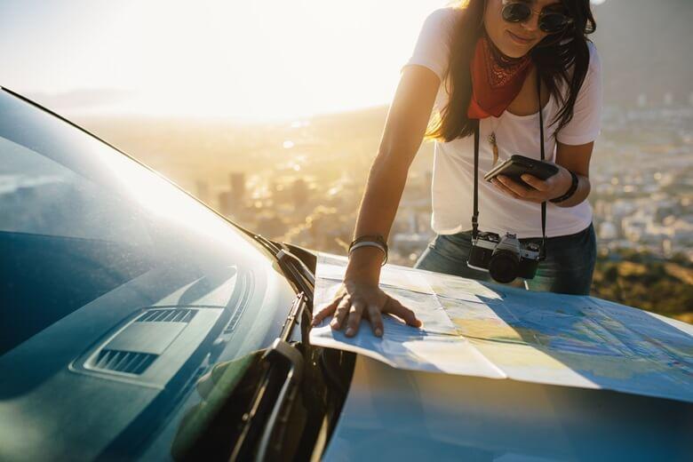Frau lehnt an einem Auto und überprüft die Autoroute