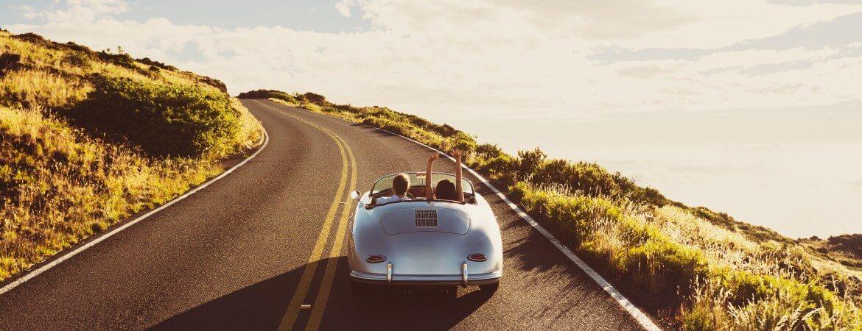 Zwei Freunde in einem Cabrio auf einer Küstenstraße