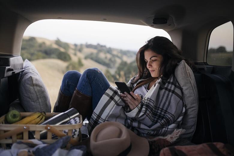 Frau sitzt mit Handy im Auto während einem Roadtrip