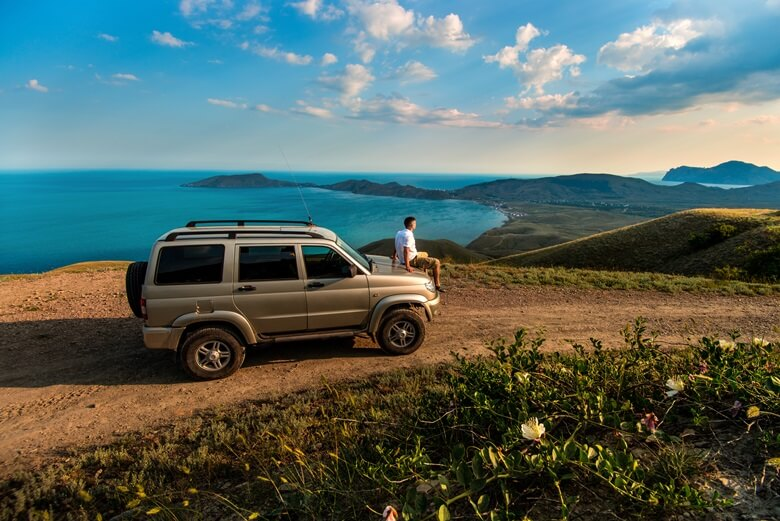 Mann sitzt auf einem Van und genießt die Landschaft