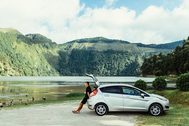 Mann steht an einem Auto und blickt auf Berge und Seen