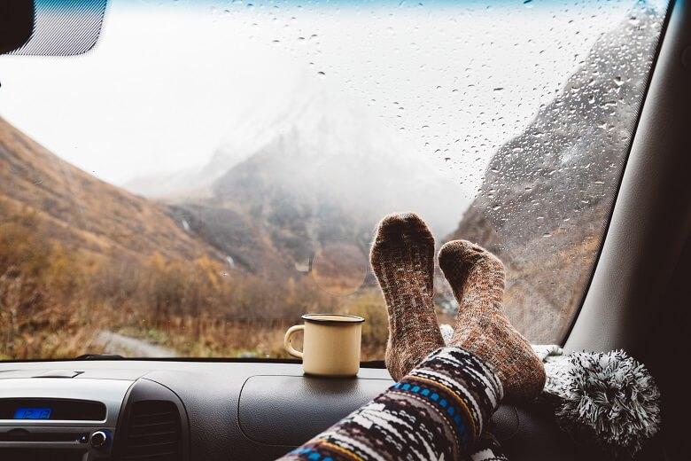 Füße und Kaffeetasse auf einer langen Autofahrt