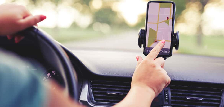 Frau bedient eine Navigations-App im Auto