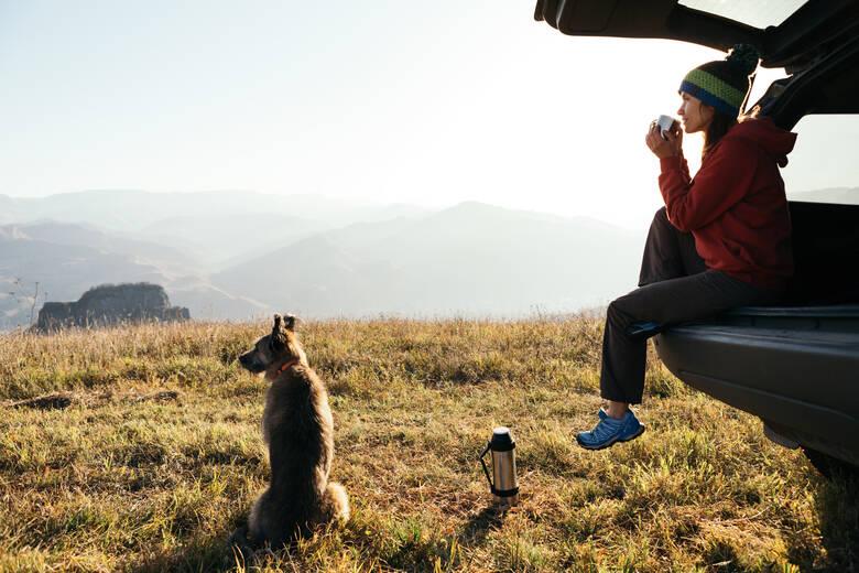 Frau und Hund an einem Auto