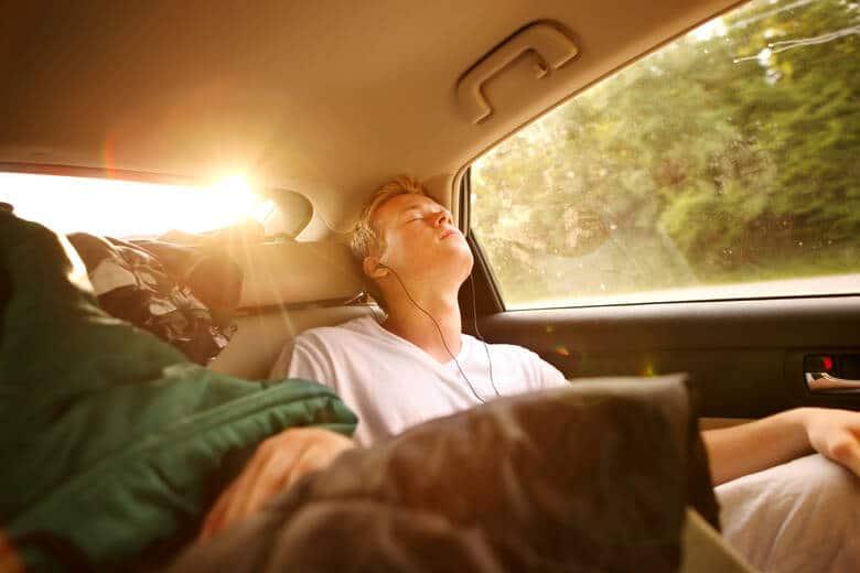 Junger Mann schläft im Auto und hört Musik