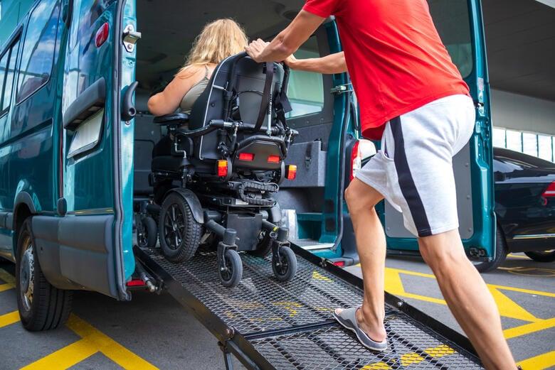 Mann leistet einer Frau im Rollstuhl Hilfe beim Einsteigen in einen behindertengerechten Van.
