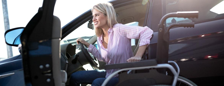 Frau mit Gehbehinderung steigt aus einem Auto.