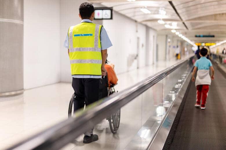 Frau im Rollstuhl erhält Hilfe im Flughafen-Terminal.