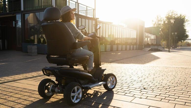 Frau fährt mit einem elektrischen Rollstuhl über das Hotelgelände.