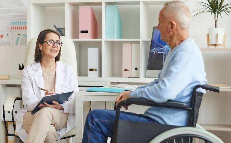 Mann im Rollstuhl beim Arztgespräch vor der Reise mit Behinderung.