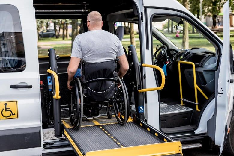 Mann im Rollstuhl wird mit einem Liftsystem in den Mietwagen gehoben.