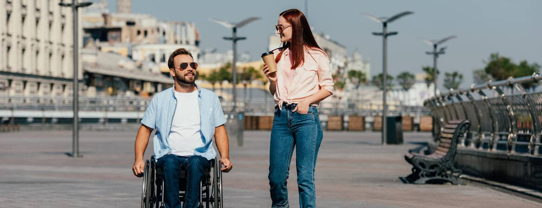 Rollstuhlfahrer und seine Begleitung sind gemeinsam unterwegs und planen die Reise.