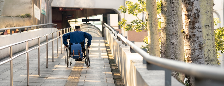 Mann im Rollstuhl fährt Auffahrt zum Bahnhof hoch.