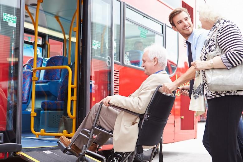 Busfahrer hilft Mann im Rollstuhl in den Bus